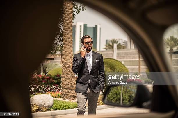 Car window view of businessman talking on smartphone outside hotel, Dubai, United Arab Emirates