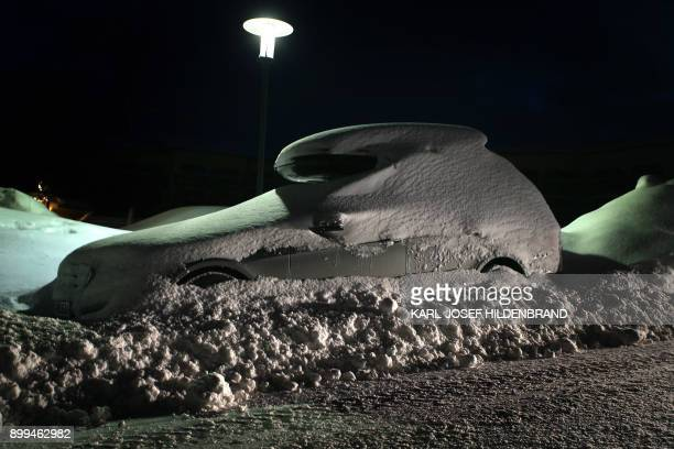 A car with a roof luggage rack is covered in snow on a parking site in Oberjoch southern Germany before sunrise on December 29 2017 / AFP PHOTO / dpa...