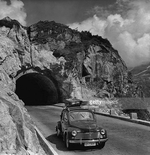 A car with baggage on the roof rack exits the newly built Susten Pass tunnel in the Swiss Alps which links Innertkirchen and Wassen in Switzerland...