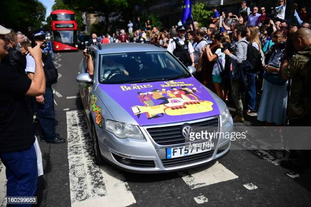 A car with Beatles decals drives over the famous zebra crossing after Beatles impersonators recreated the iconic 'Abbey Road' photograph made 50...