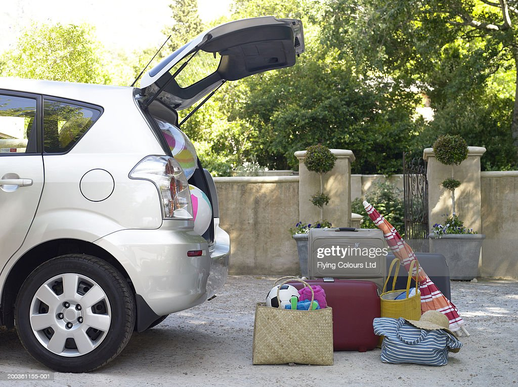 Car with boot open and beach equipment and cases : Stock Photo