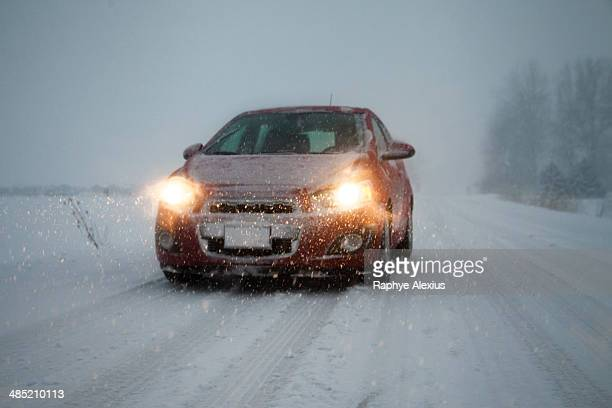 Car with headlights on driving along foggy snow covered road
