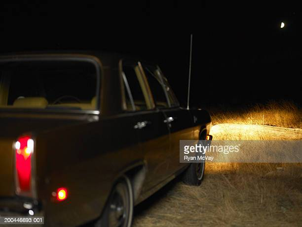 car with headlights on parked in tall grass, night, rear view - abandoned car stock photos and pictures