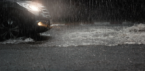 Car with headlights run through flood water after hard rain fall at night. 1147297017