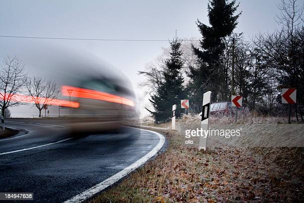Car with red brake lights is passing a curve