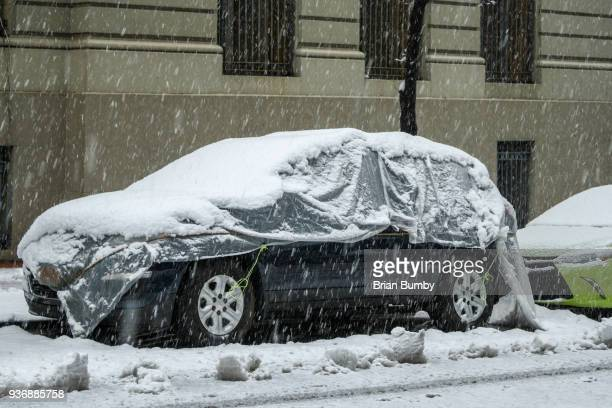 Car with snow cover on street