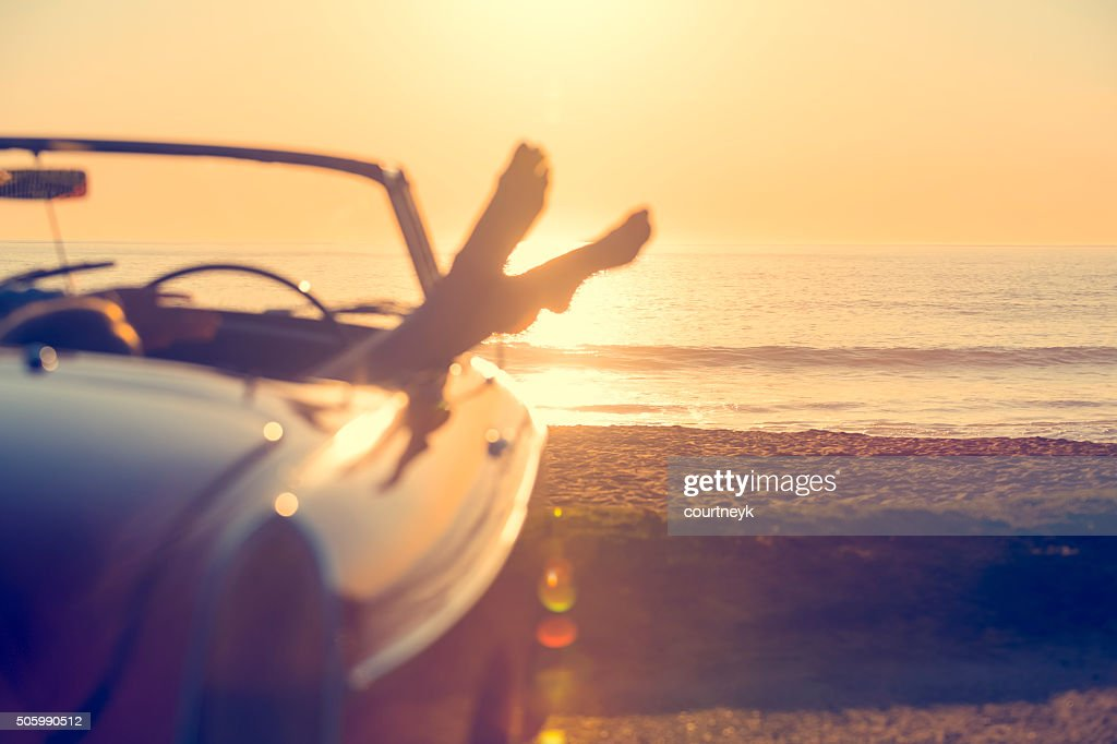 Car with womans feet hanging out of the window : Stock Photo