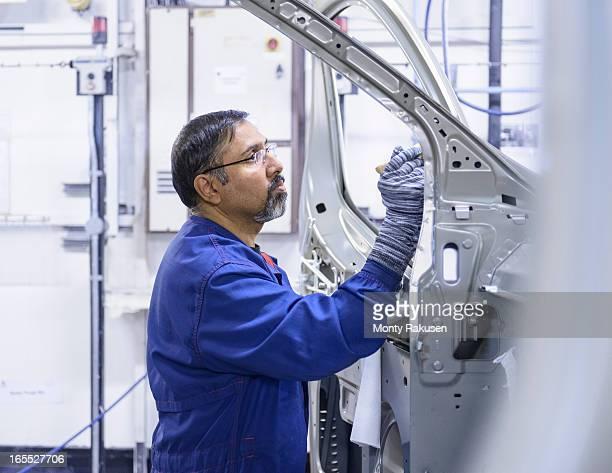 Car worker applying sealant to car body in car factory