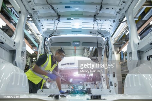 Car worker wearing high visibility jacket fitting parts on vehicle on production line in car factory