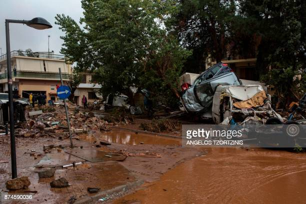 Car wreckages are piled up in a flooded street of Mandra northwest of Athens on November 15 after heavy overnight rainfall At least 14 people died on...