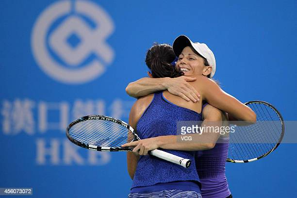 Cara Black of Zimbabwe and Caroline Garcia of France embrace as they compete with Sara Errani of Italy and Roberta Vinci of Italy during day five of...