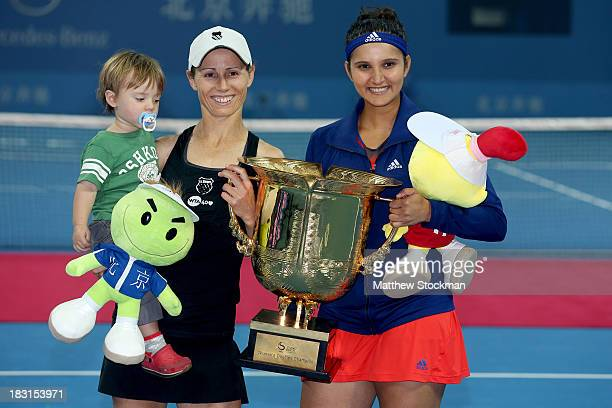 Cara Black of Zimbabwe, holding her son Lachlan, and Sania Mirza of India pose for photographers after defeating Vera Dushevina and Arantxa Parra...