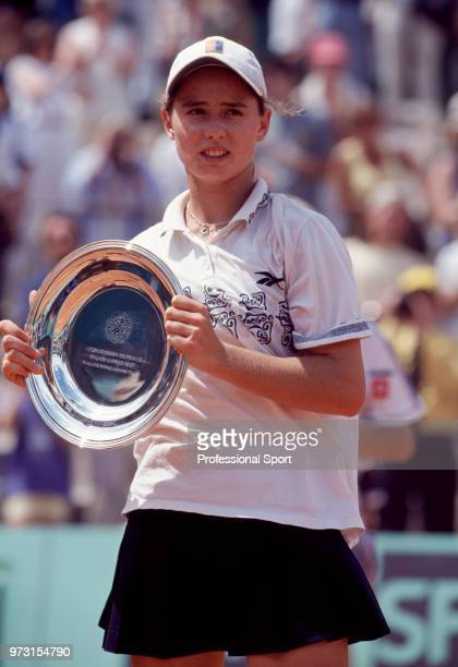 Cara Black of Zimbabwe poses with the runner-up trophy after being defeated by Justine Henin of Belgium in the Girls' Singles Final of the French...