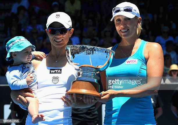 Cara Black of Zimbabwe with her son Lachlan and Anastasia Rodionova of Australia pose with the trophy following their doubles final against Julia...