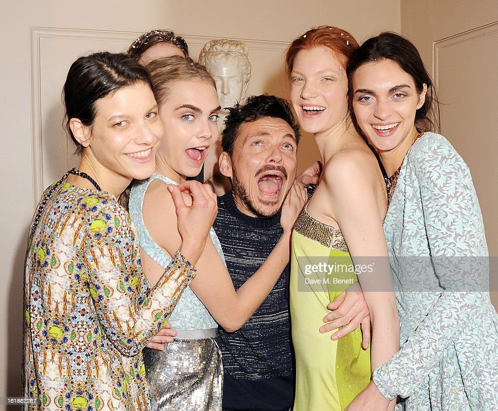 Cara Delevingne (2R) and Matthew Williamson (C) pose with models backstage at the Matthew Williamson show during London Fashion Week Fall/Winter 2013/14 at the Royal Opera House on February 17, 2013 in London, England.
