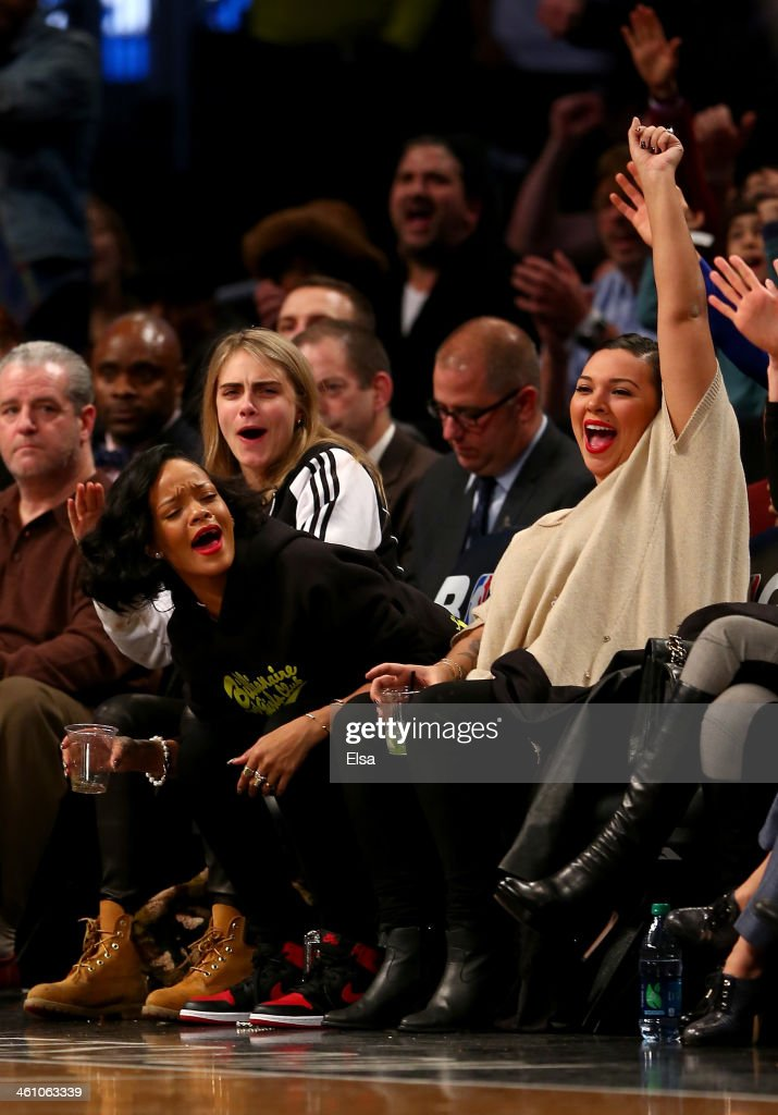 Cara Delevingne, Rihanna and Jennifer Rosales celebrate in the second half of the game between the Brooklyn Nets and the Atlanta Hawks at the Barclays Center on January 6, 2014 in the Brooklyn borough of New York City.