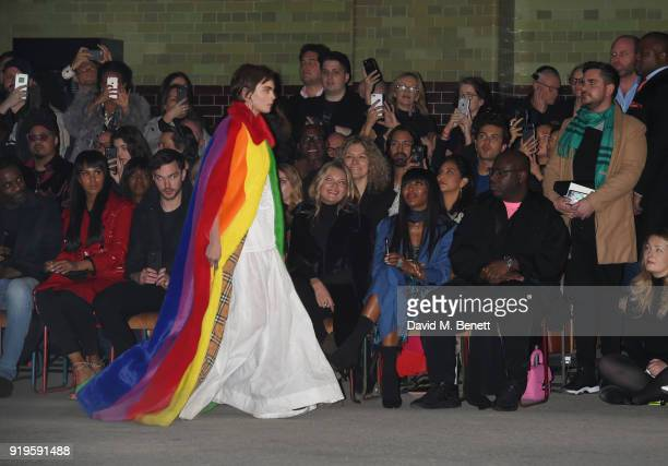 Cara Delevingne walks the runway as Idris Elba Sabrina Dhowre Nicholas Hoult Naomi Watts Kate Moss Naomi Campbell and Steve McQueen look on at the...