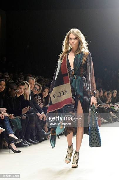 Cara Delevingne walks the runway as Naomie Harris Tinie Tempah Harry Styles Alison Mosshart Mario Testino Jamie Campbell Bower and Angelababy look on...