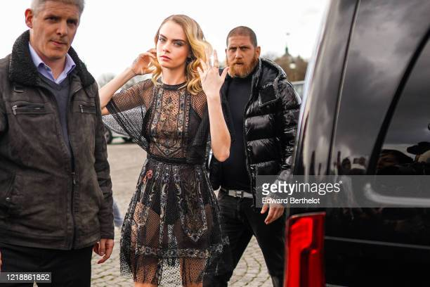 Cara Delevingne wears a black lace mesh dress with floral embroidery, outside Dior, during Paris Fashion Week - Womenswear Fall/Winter 2020/2021, on...