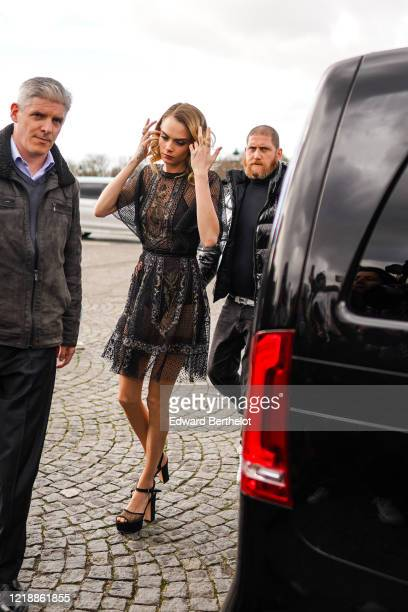 Cara Delevingne wears a black lace mesh dress with floral embroidery, shoes, outside Dior, during Paris Fashion Week - Womenswear Fall/Winter...
