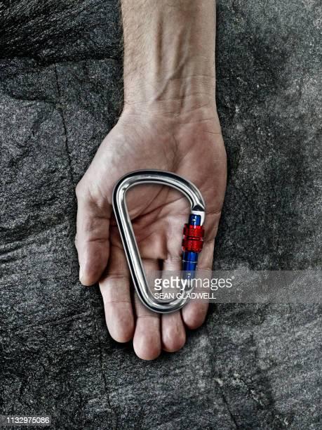 carabiners in hand - betrouwbaar stockfoto's en -beelden