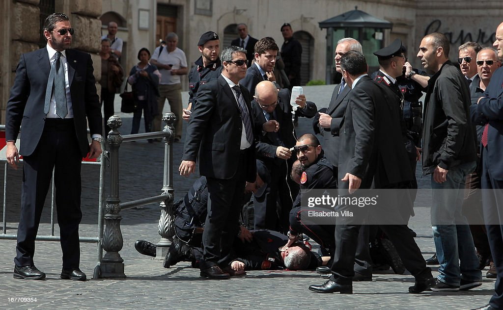 A Carabiniere police officer lies on the ground after being shot outside the Chigi Premier's office on April 28, 2013 in Rome, Italy. Two military police officers were shot in the square outside Palazzo Chigi while the new government of Enrico Letta was being sworn in. The attacker was caught and the authorities identified him as Luigi Preiti a unemployed man born in 1964 in Calabria.