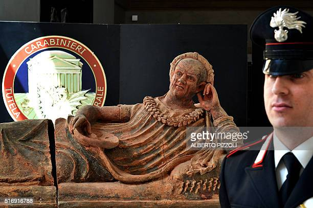 A Carabiniere stand next to recovered archaeological artifacts in Rome on March 22 2016 Italian and Swiss art police have busted open an...