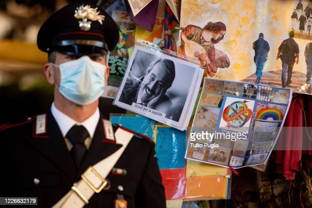 Carabiniere wears a face mask while standing in front of the Falcone Tree during the commemoration ceremony of the 28th anniversary of the Capaci...