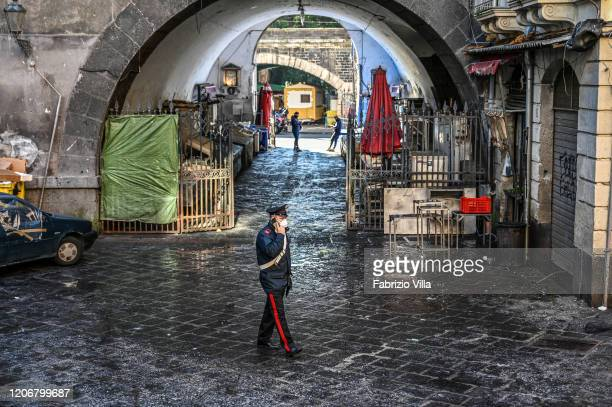 Carabiniere with a protective mask speaks on the phone at the traditional openair fish market a piscaria closed due to the Coronavirus emergency on...