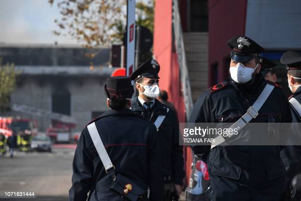 Carabinieri gendarmes wear protecting masks as they intervene after a fire broke out overnight at the TMB Salario mechanical biological waste...
