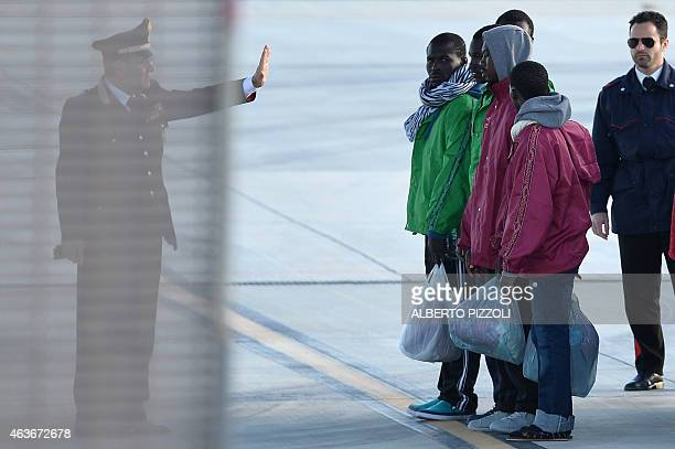 Carabinieri gives instructions to migrants before they board a military plane to be transferred on February 17, 2015 at the Lampedusa airport....