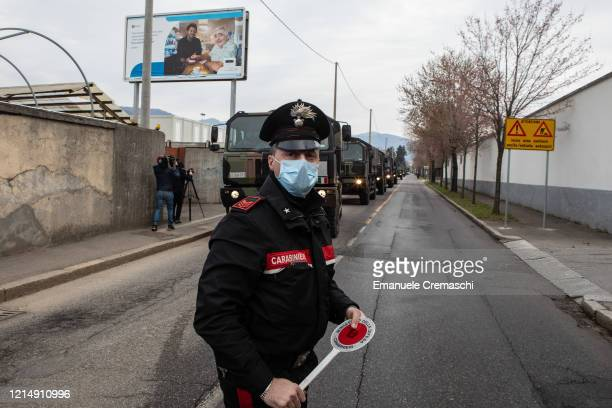 Carabinieri officer blocks the road traffic as a convoy of military vehicles arrives at the Monumental Cemetery on March 26 2020 in Bergamo near...