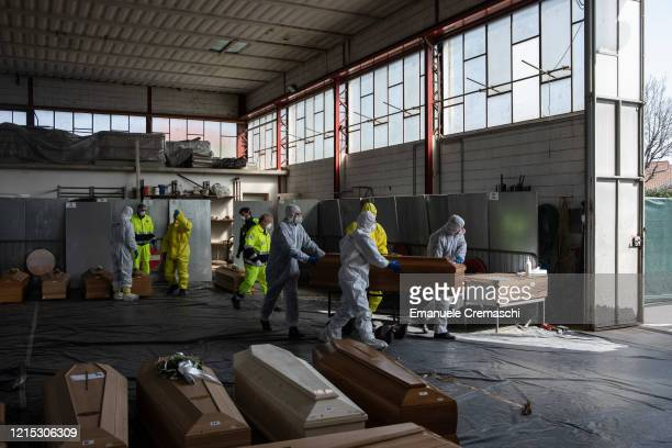 Carabinieri officers, wearing protective suits, pull a coffin on March 28, 2020 in Ponte San Pietro, near Bergamo, Northern Italy. The Italian Army...