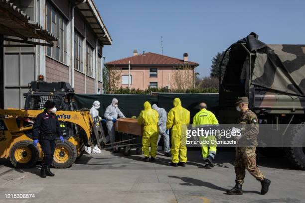 Carabinieri officers wearing protective suits pull a coffin on March 28 2020 in Ponte San Pietro near Bergamo Northern Italy The Italian Army has...