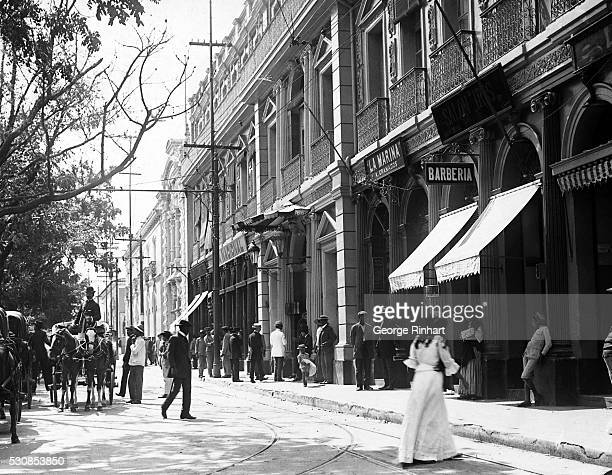Caracas VenezuelaORIGINAL CAPTION READS A street scene in the city people stand by store fronts while horsedrawn carriages fill the road Early 20th...