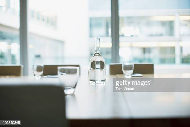 Carafe and glasses on empty modern conference room in office