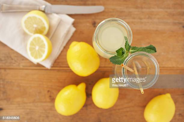 Carafe of lemon juice, sliced and whole lemons on wood, elevated view