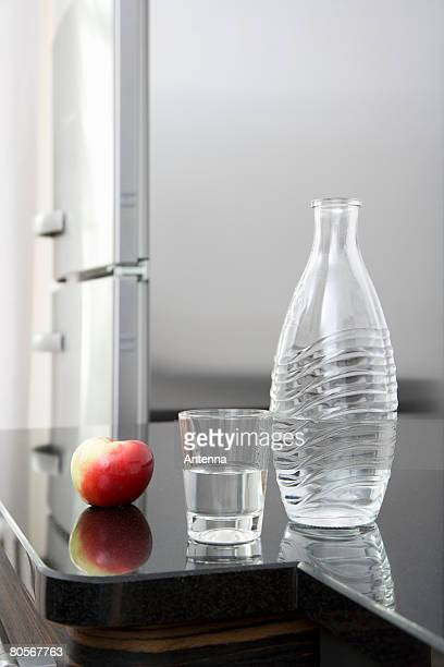 A carafe of water, a glass and an apple on a counter