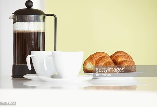 Carafe with coffee cups and croissants
