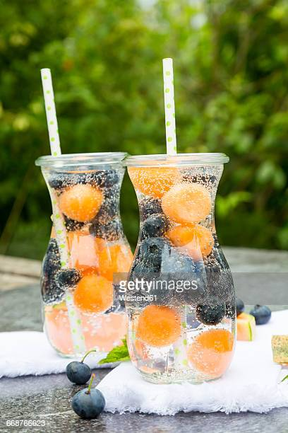 Carafes of infused water with blueberries and melon