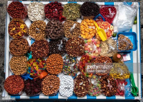 Caramelized peanuts chocolates and candies are sold at a stand on a street in Mexico City on October 21 2016 / AFP PHOTO / OMAR TORRES