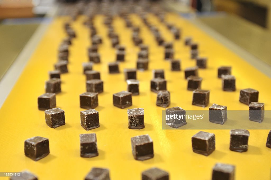 Caramels on a conveyor belt : Stock Photo