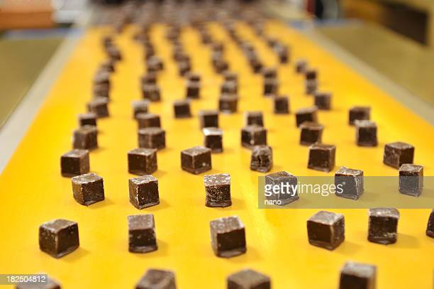 caramels on a conveyor belt - chocolate factory stock photos and pictures