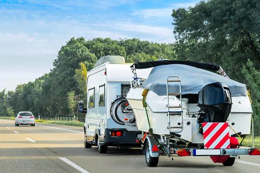 Caravan and trailer for motor boats on road in Switzerland 838525562