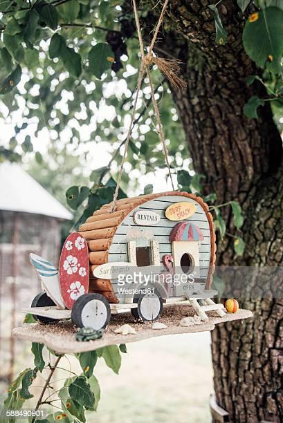 caravan bird houses hanging in a tree - vogelhäuschen stock-fotos und bilder