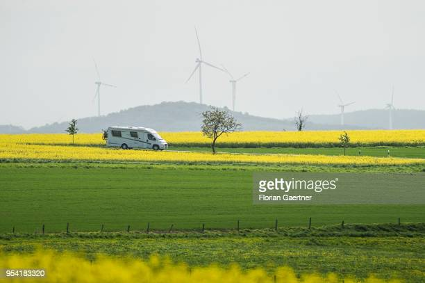 A caravan drives along a street between fields of rape on April 30 2018 in Schoepstal Germany