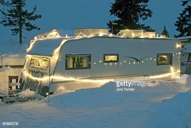 Caravan in snow covered in Christmas lights