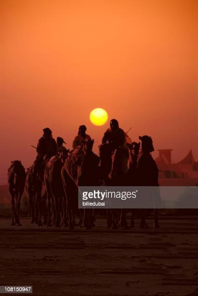 Caravan de personnes voyageant sur des chameaux au coucher du soleil