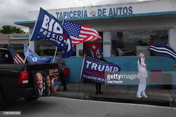 Caravan of supporters for Democratic presidential nominee Joe Biden drive past supporters of President Donald Trump standing on the sidewalk next to...