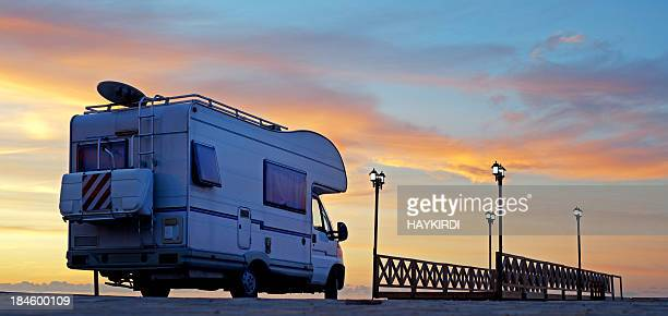 Caravan on the road at sunset